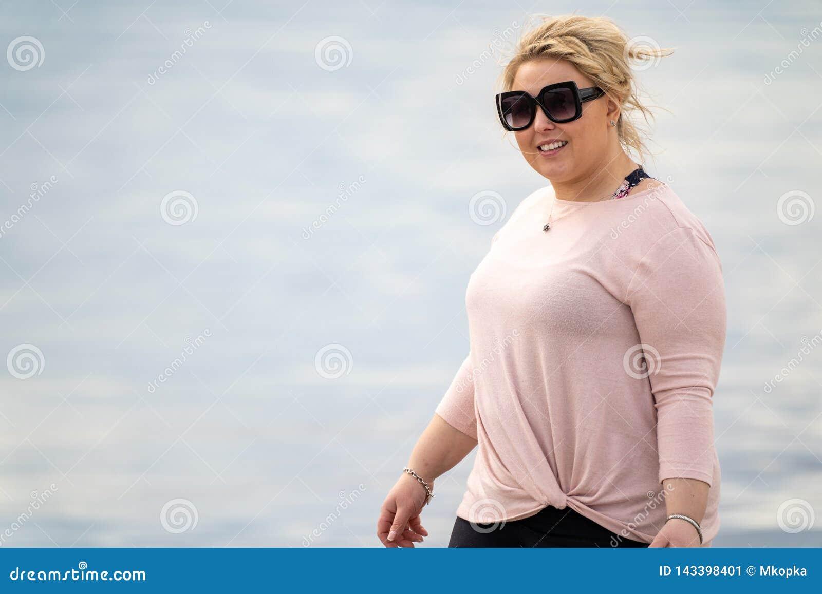 Blonda iklädda tillfälliga kläder för den vuxna kvinnan promenerar kusten av stranden