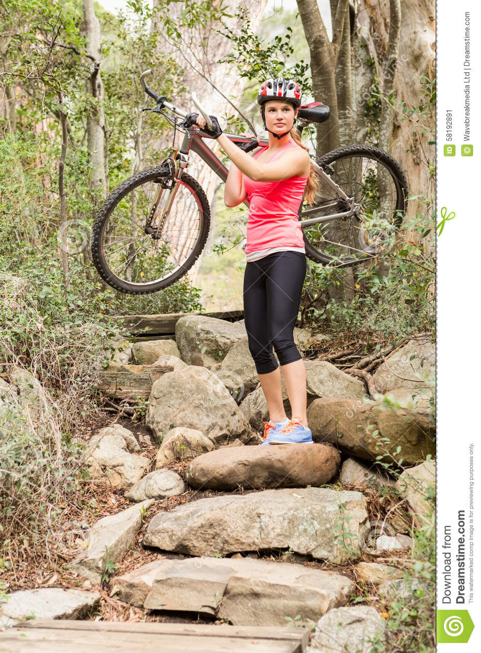 Blonde athlete carrying her mountain bike over rocks