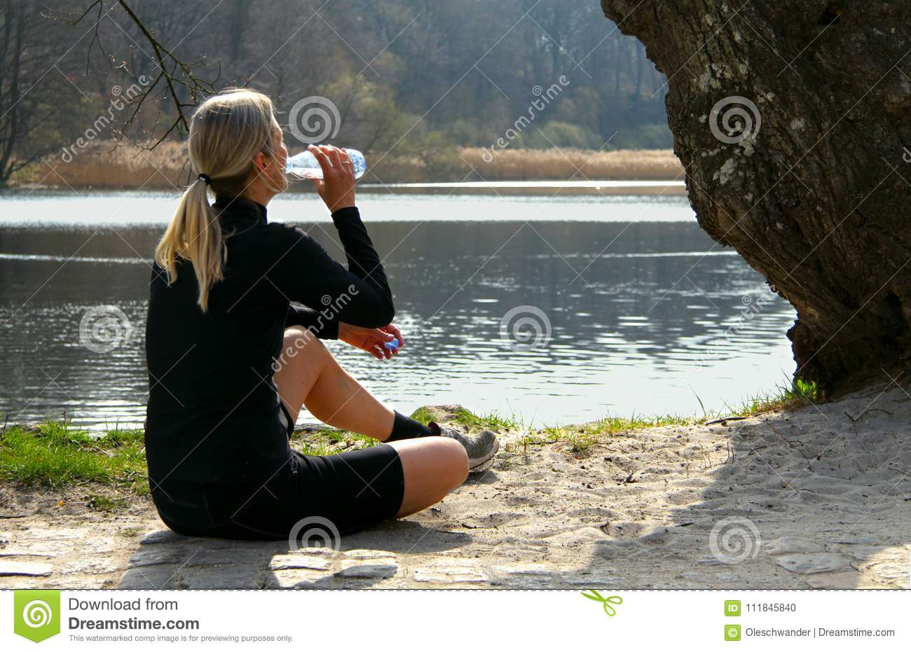 Blonde athlete girl sitting on ground to relax after jogging drinking water under a tree on a lake shore