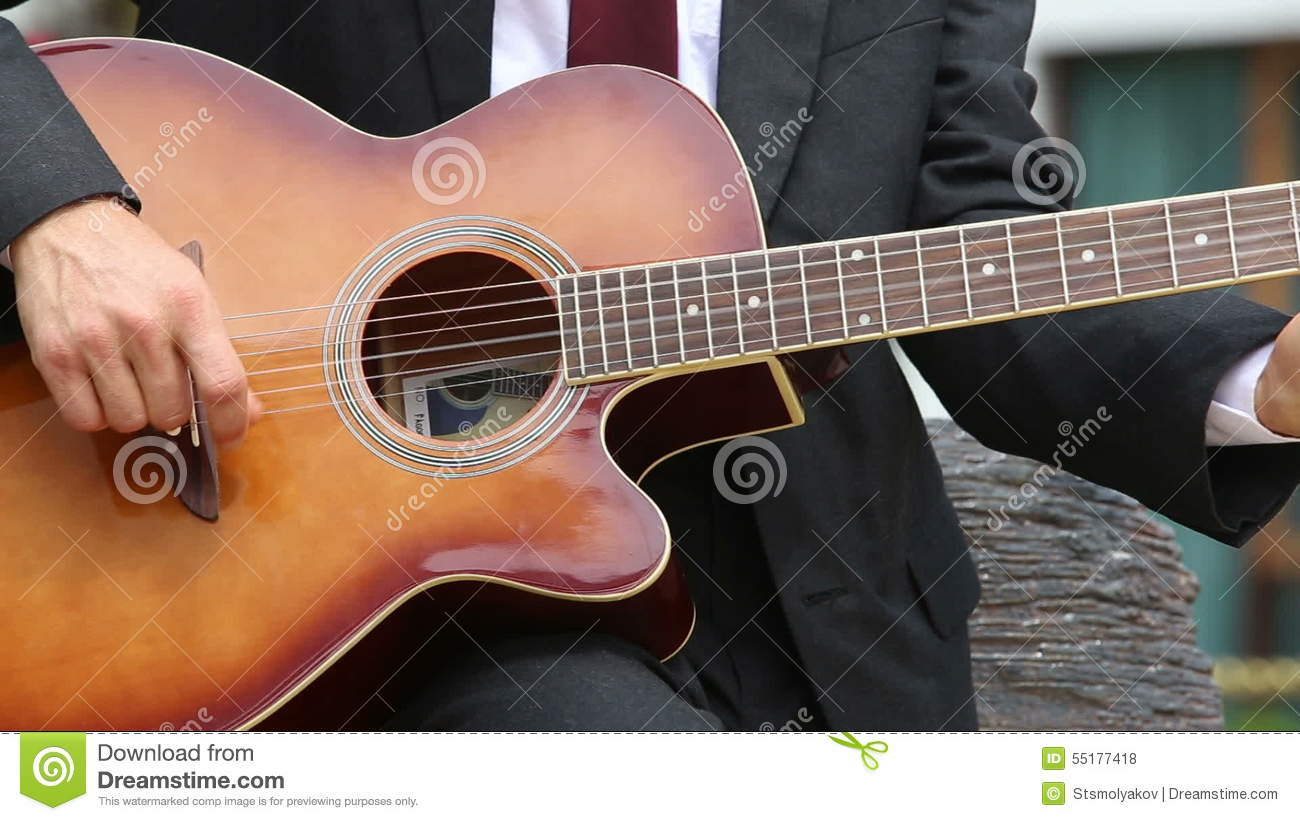 Blonde Bearded Man In Black Suit And Glasses Plays Guitar Chords