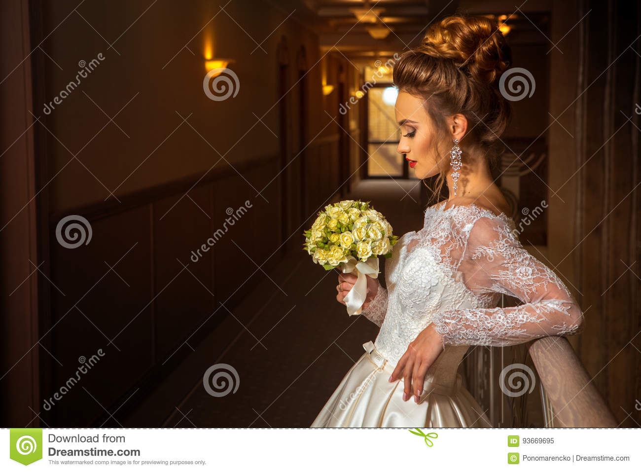 Blonde beautiful bride in fashionable wedding dress with bouquet of roses
