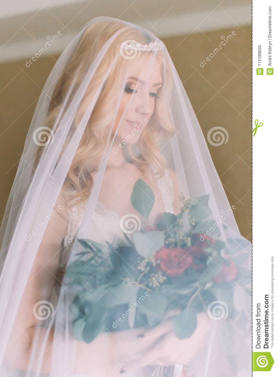 26b2ee0785a Blonde bride with long veil dressed in white underwear standing on the bed  and holding wedding bouquet.
