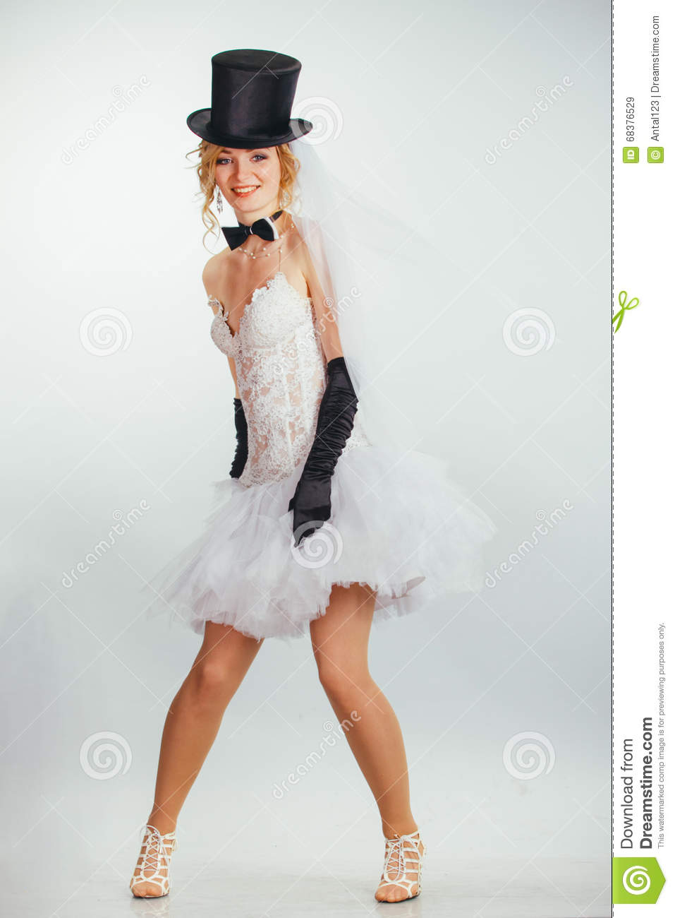 521a729d18f45 Young beautiful blonde bride in tophat with veil and stylish wedding dress  with long black gloves
