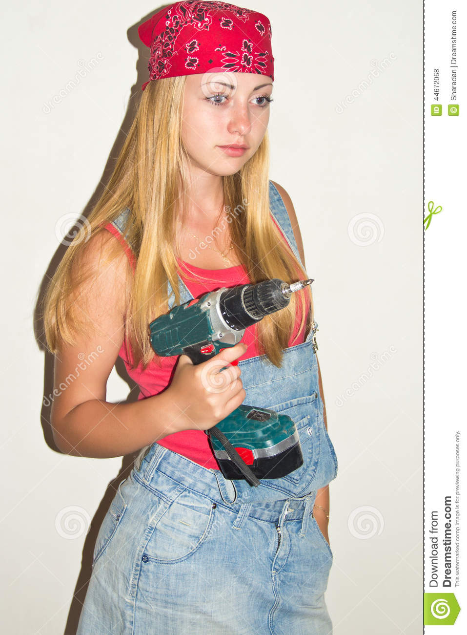 4f911be332 The photo shows a young beautiful girl. Her bandana and denim sundress. In her  hands drill