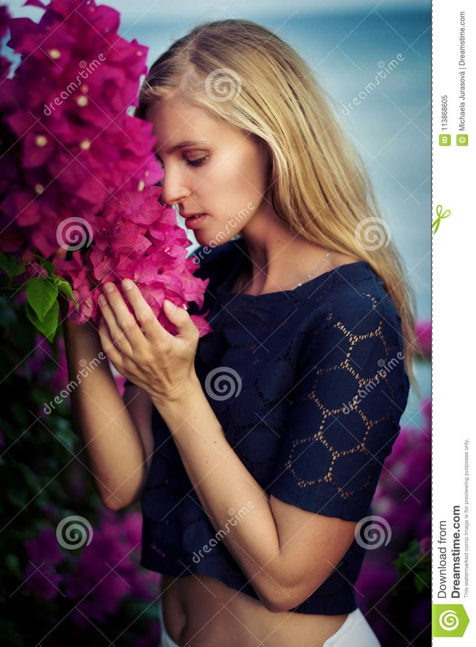 Blonde Caucasian Woman Wearing Dark Blue Lace Top And White Skirt In Crop Posing Between Pink Flowers By The Sea Egypt Long Hair Smile