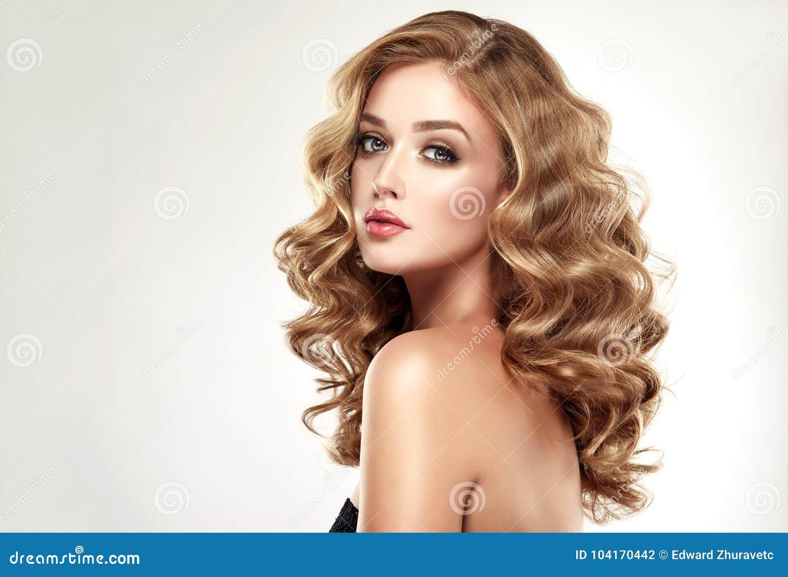 Blonde de femme avec la coiffure volumineuse, brillante, bouclée et lâche