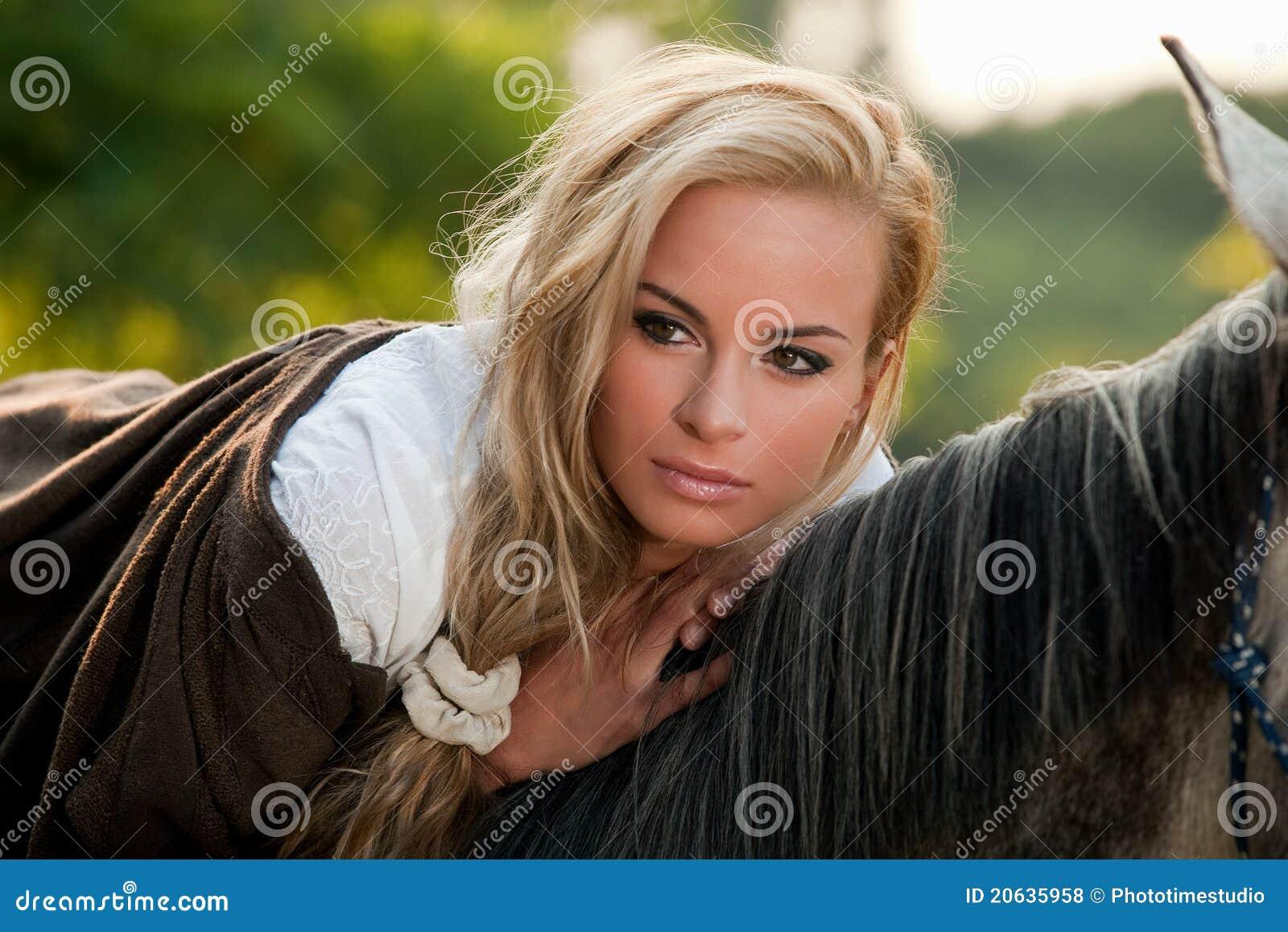 Die junge blonde frau die ein stillsteht unterst tzen vom pferd