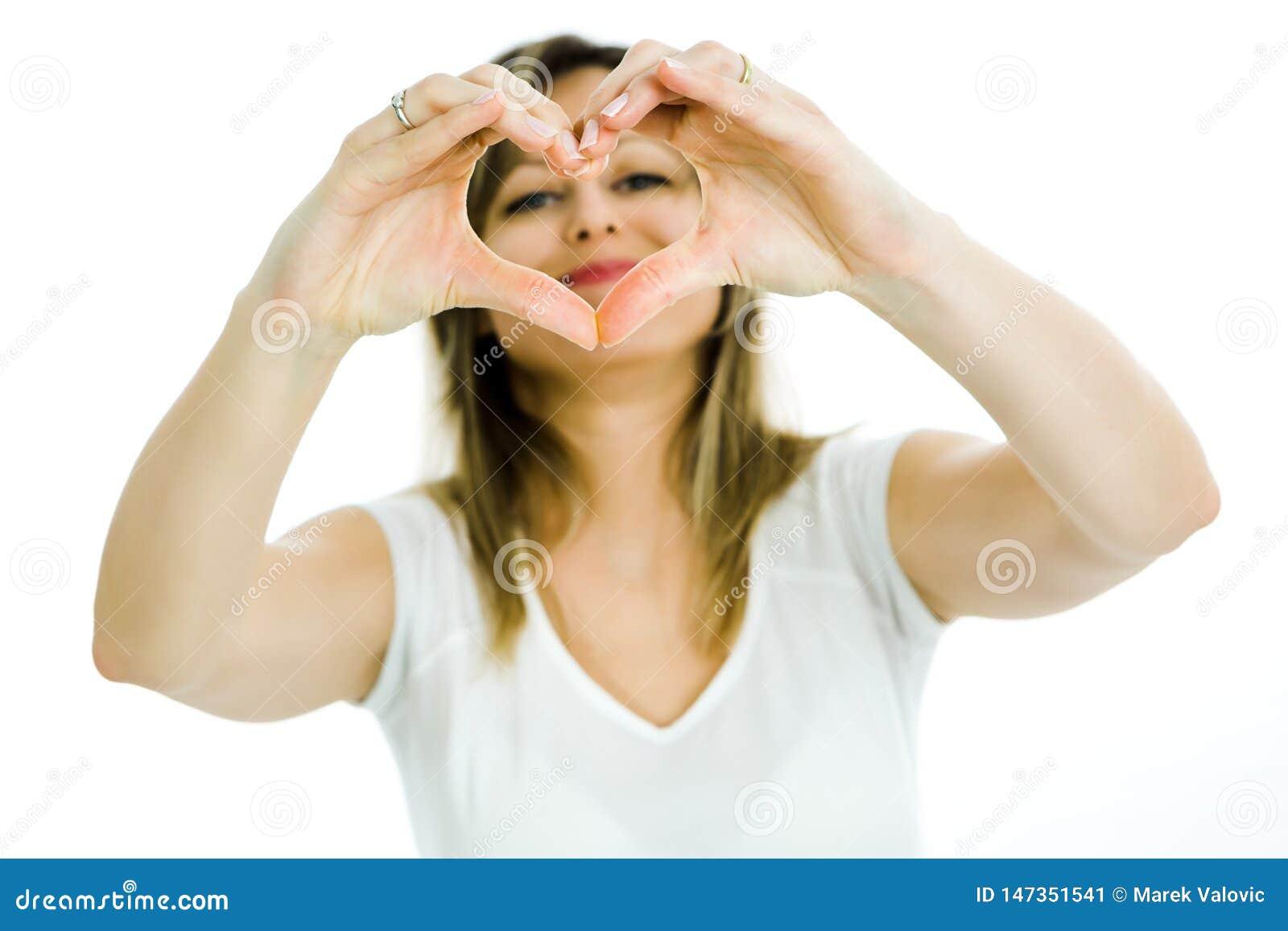 Blonde Frau zeigt Herzform mit den Händen - schauend durch das Herz