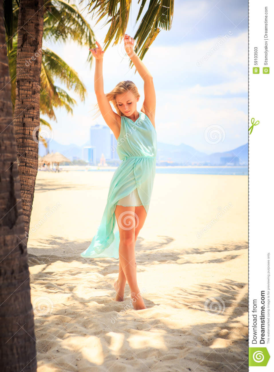 European slim blonde girl barefoot in light azure transparent frock stands  near palms with hands on breast on beach
