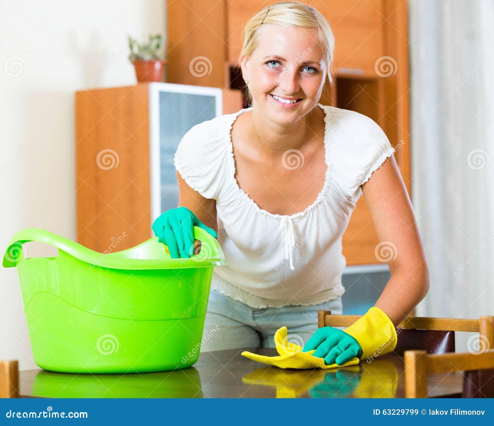 Blonde girl dusting in living room