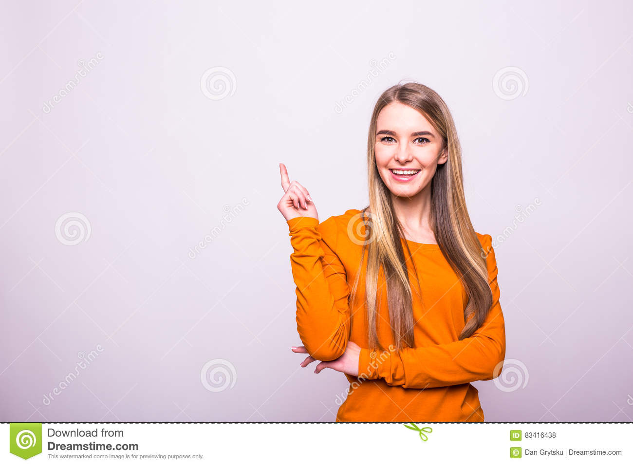 blonde girl in orange t-shirt pointed with finger up on white