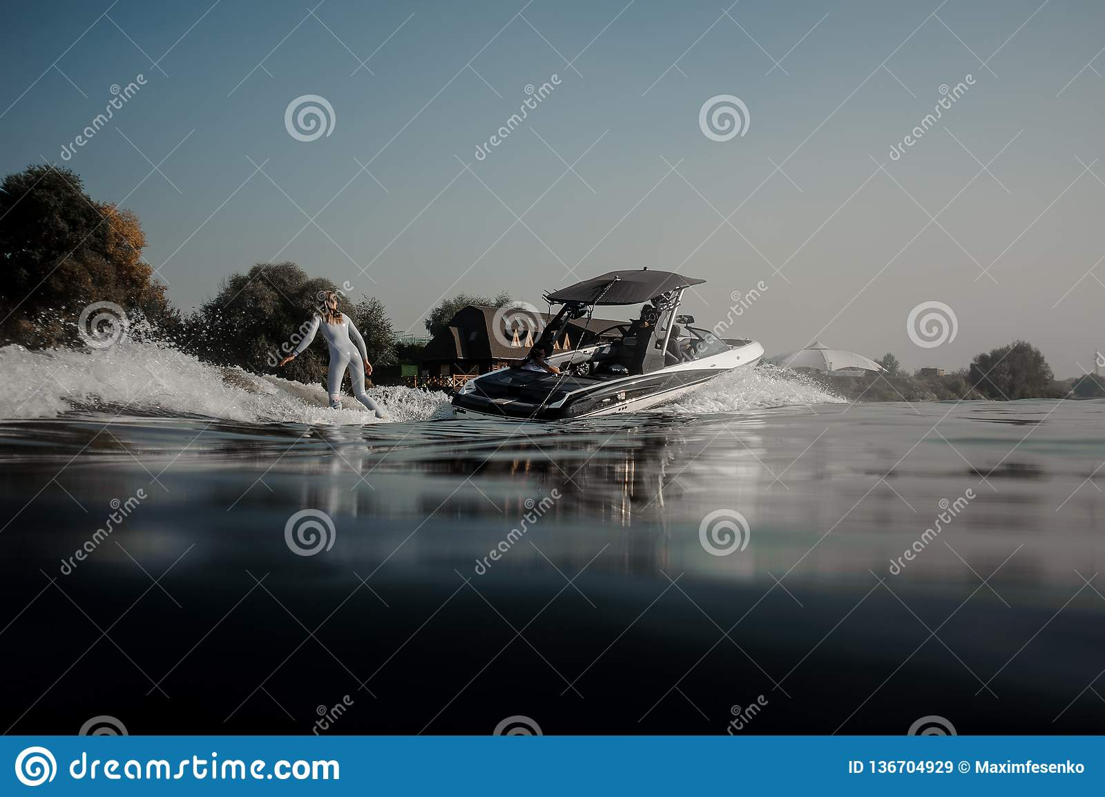 Blonde girl riding on the wakeboard holding a rope on the motorboat