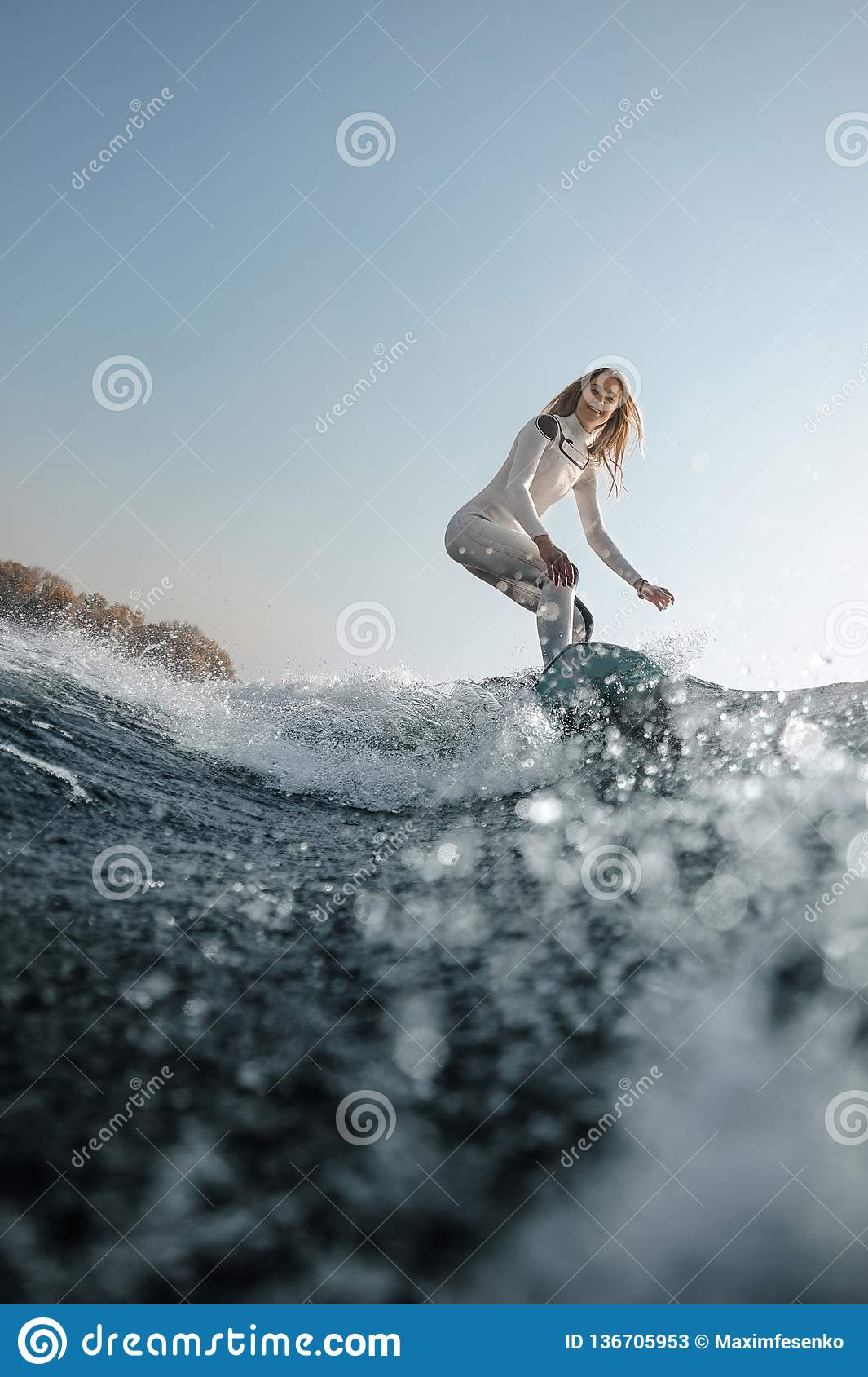 Blonde girl riding on the wakeboard on the river
