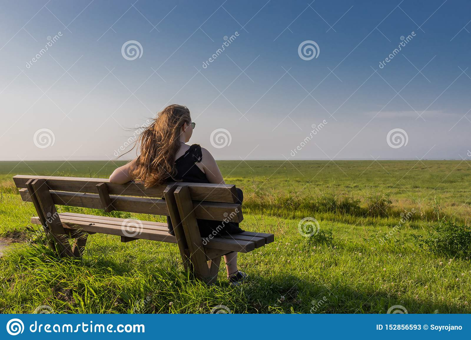 Blonde girl sitting on a bench
