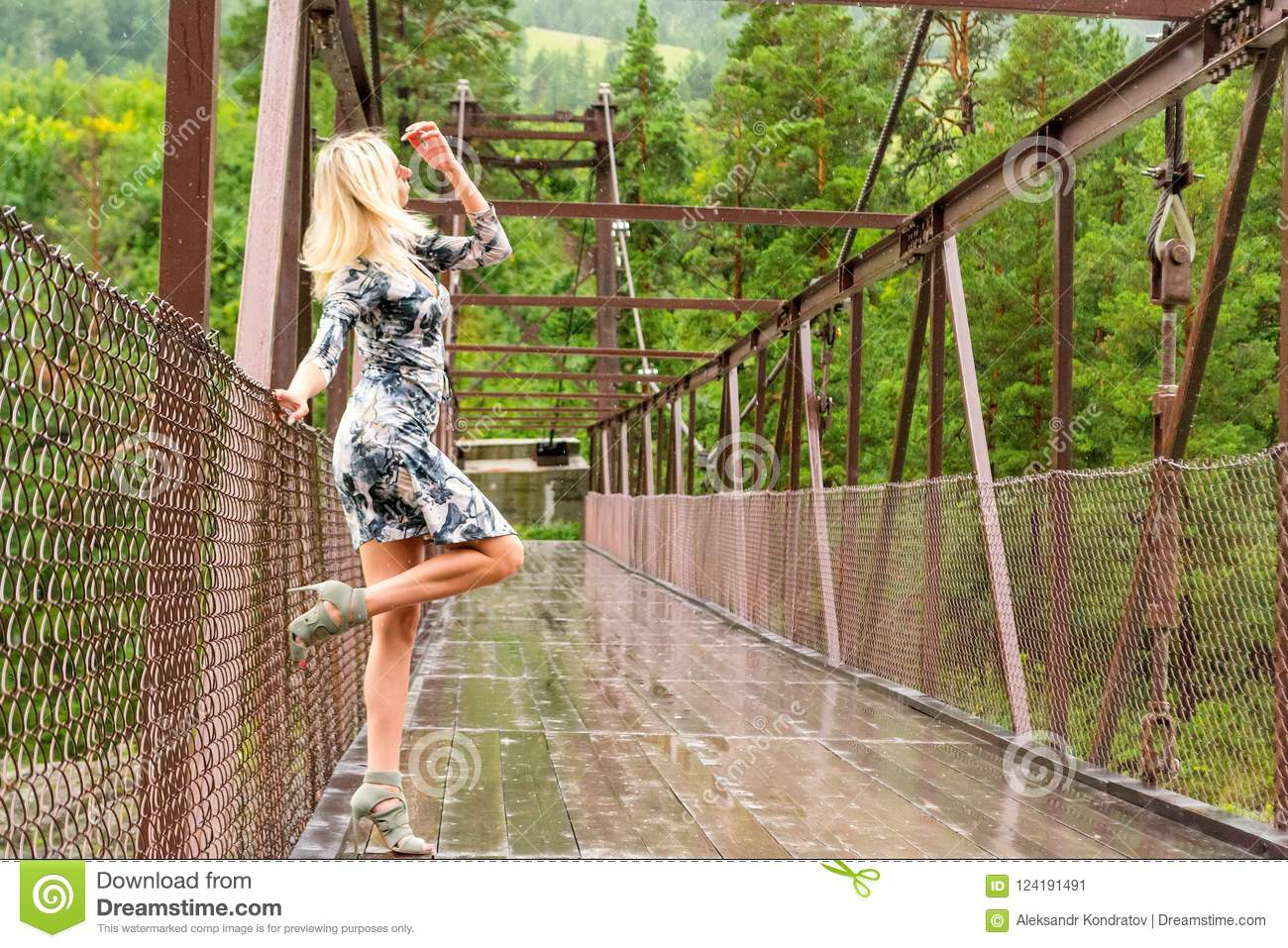 Blonde girl stands on a bridge constructed of metal and wood the