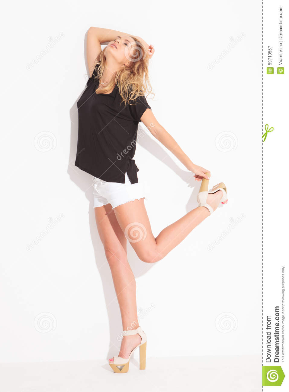 Blonde Girl Wearing Short Pants Looking Up While Holding Her Hee Stock Image Image Of Look Black 59713557