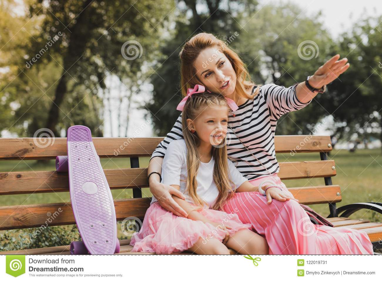 Blonde-haired caring mother showing her girl nice cafe