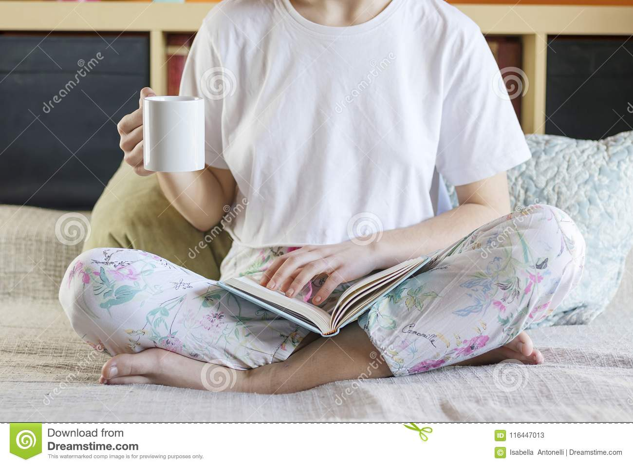 8216b1aab46f Blonde-haired pretty lady in pajamas is drinking her morning coffee sitting  on bed