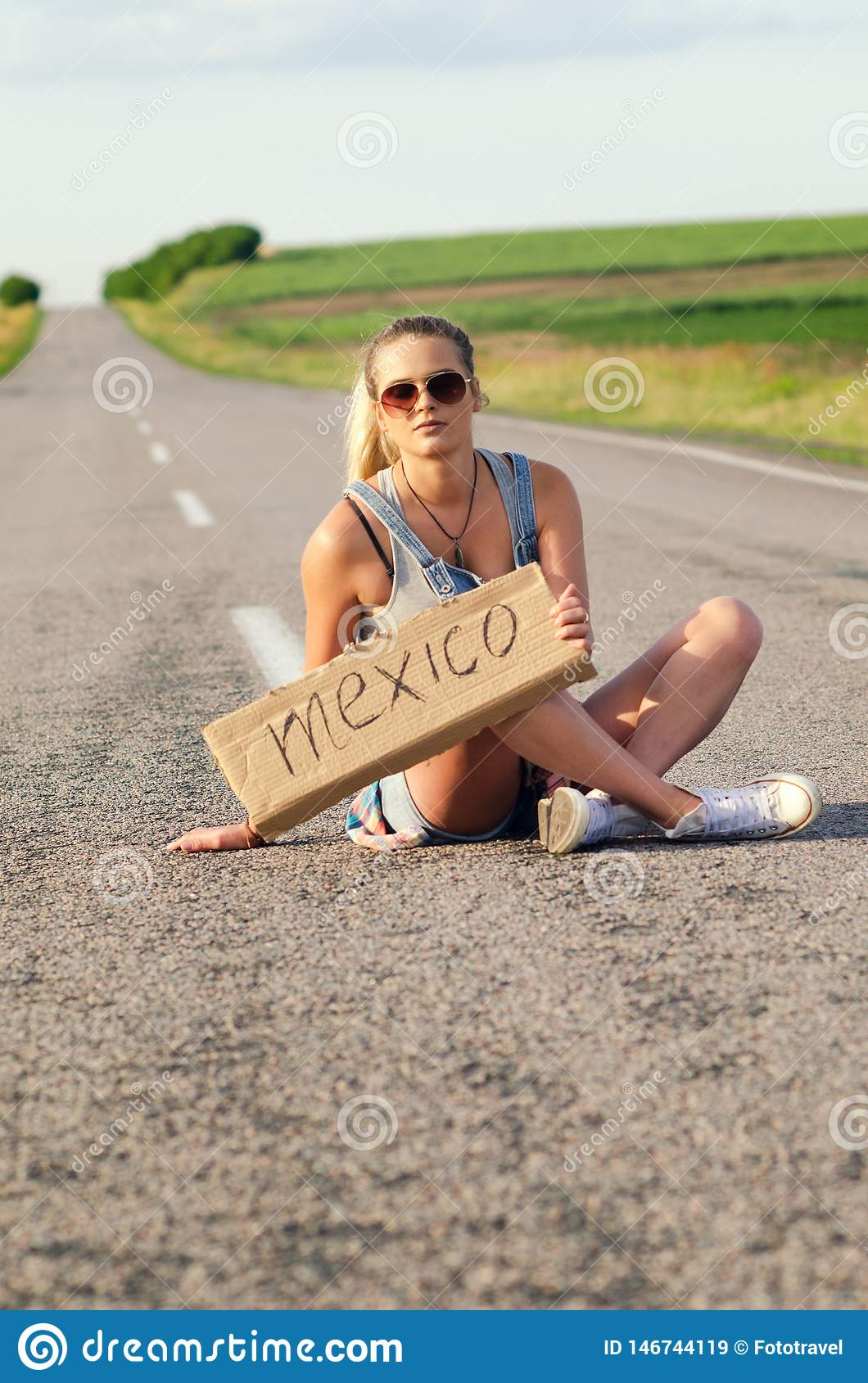Beautiful Girl Hitchhiking On The Road Traveling