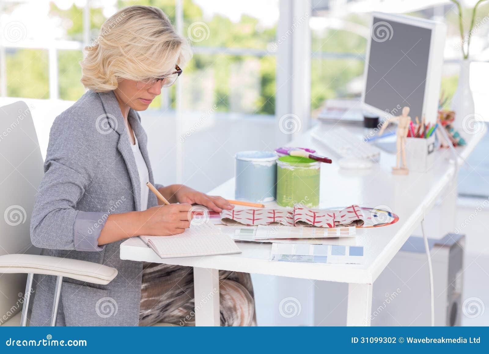 Blonde interior designer working on her desk stock for Work for interior designer