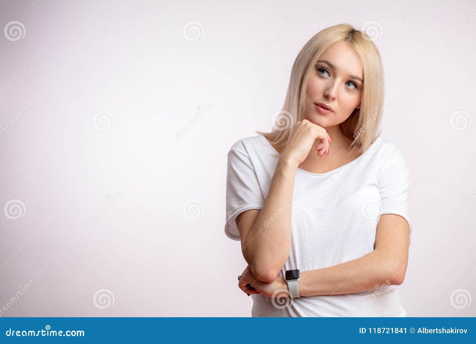 Blonde joven pensativo con la mano en la barbilla