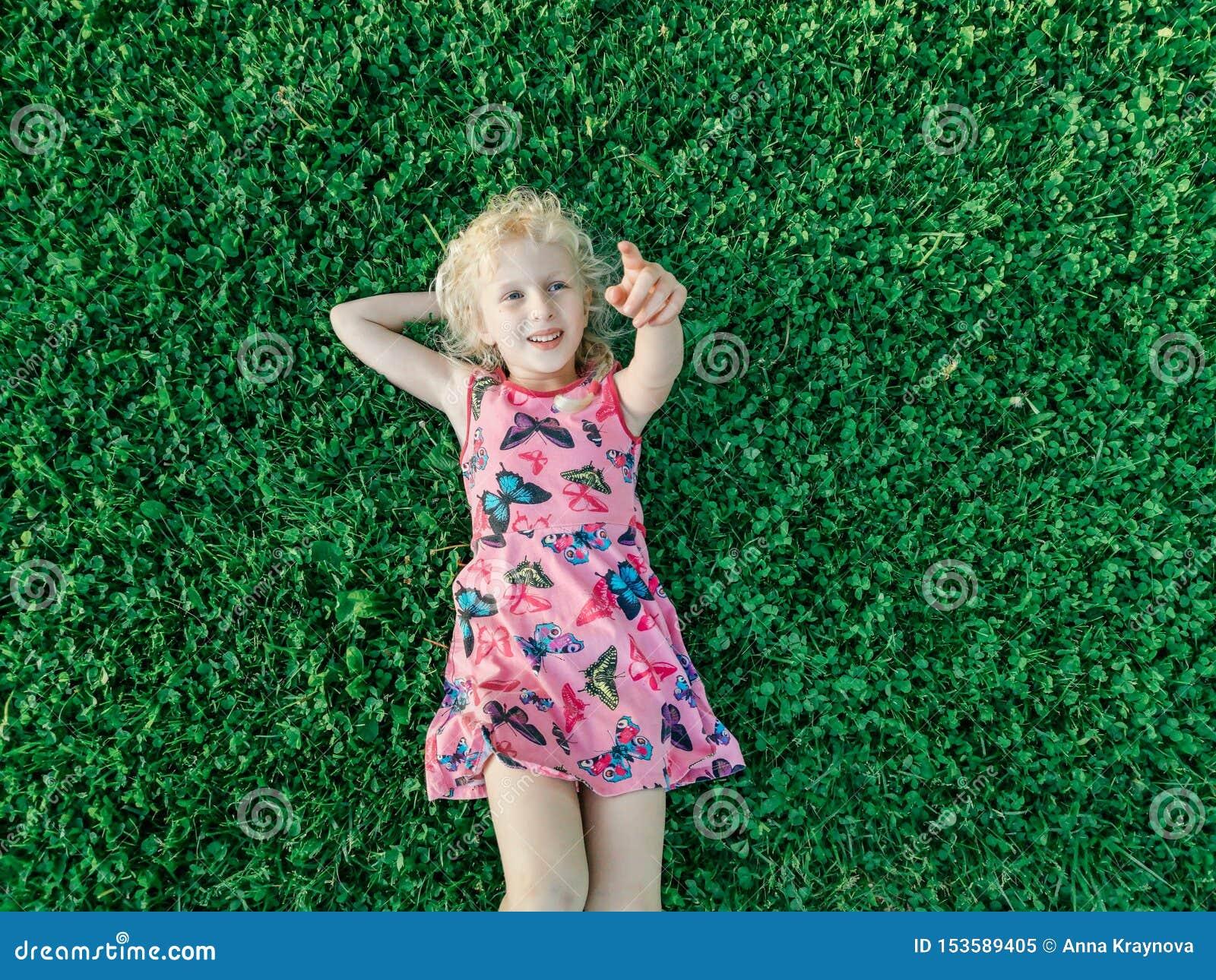 Blonde Kaukasisch glimlachend meisje in rode roze kleding die op gras liggen die met vinger richten