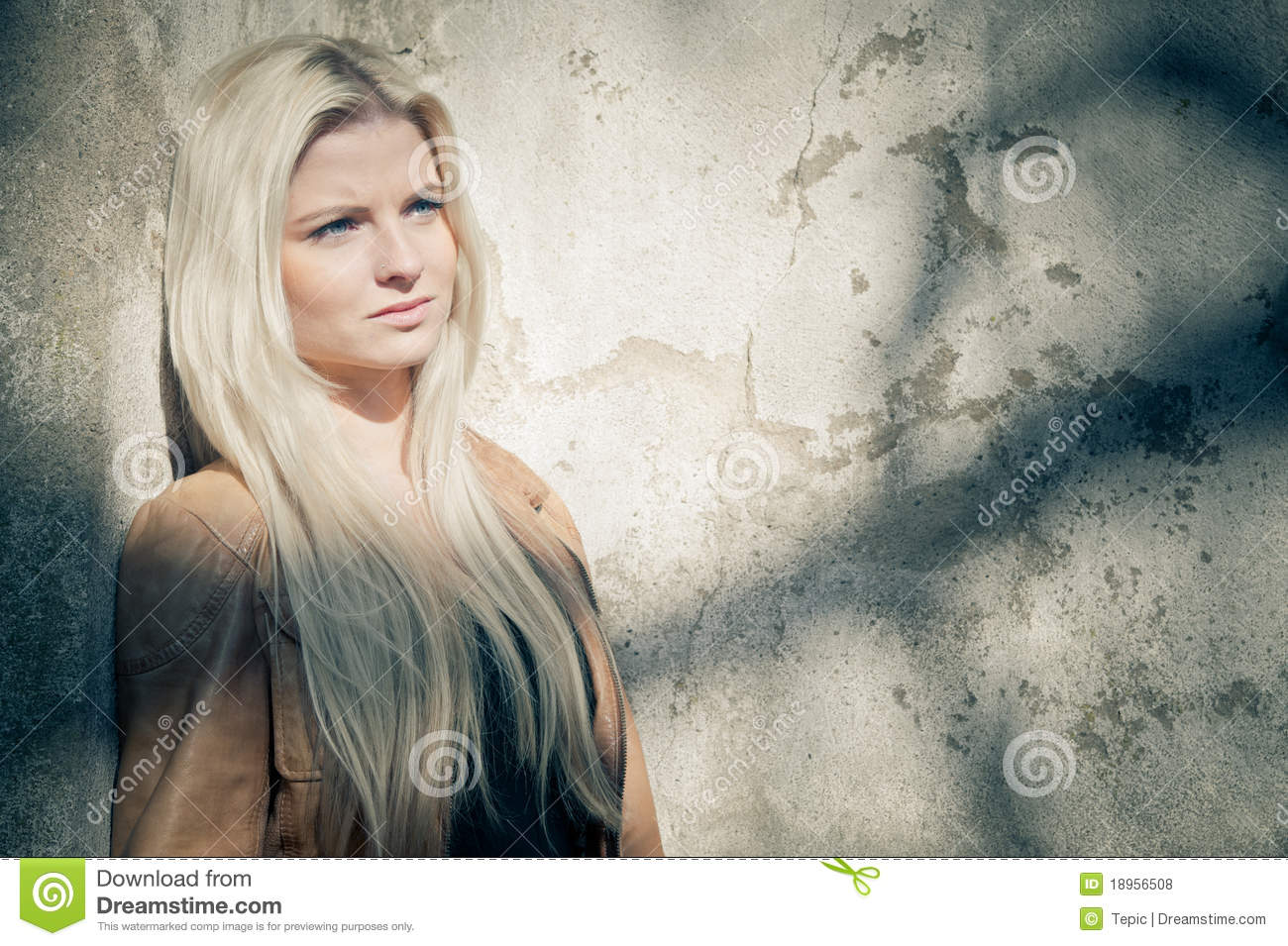 Blonde leaning on grungy Wall