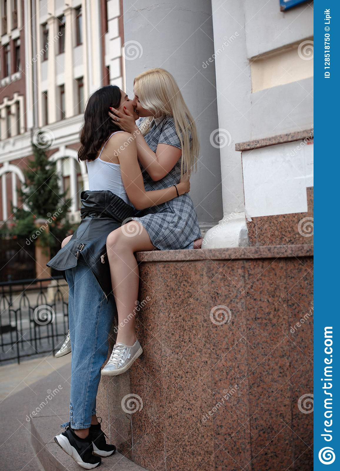 Blonde lesbian sitting on wall and kissing her brunette girlfriend.  Spending time in the city.