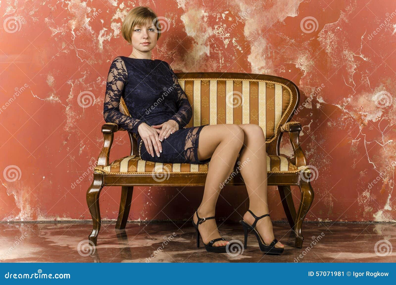 Blonde met kort haar in blauwe overall met kantkokers en sandals met hoge hielen