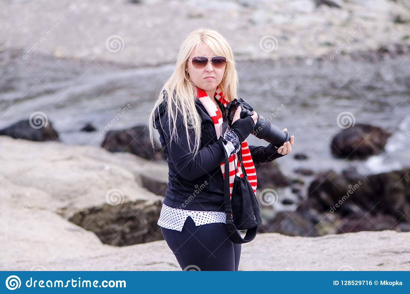 A blonde female photographer looks angry and upset
