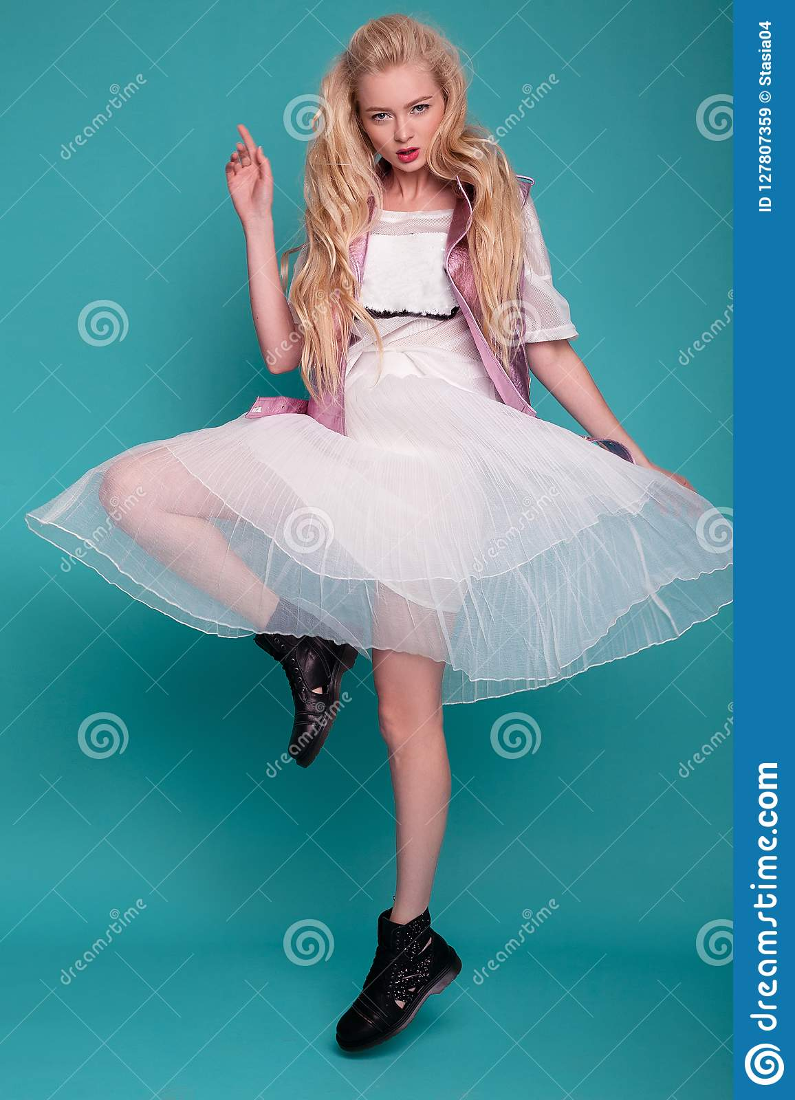 Blonde model in white dress and black boots posing on blue background.
