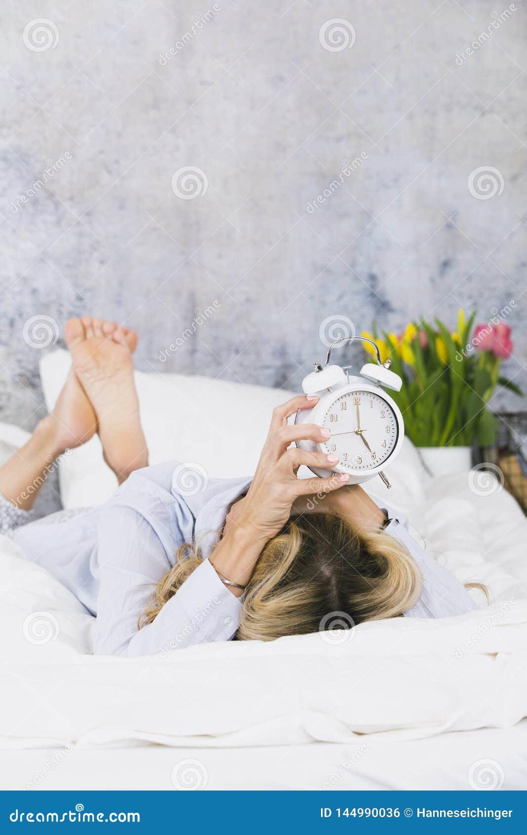 Blonde, recht junge Frau mag nicht morgens aufstehen und hasst ihren Klingelnwecker und wird frustriert