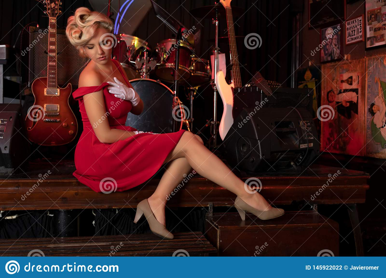 Sexy blonde sitting on a stage in front of musical instruments