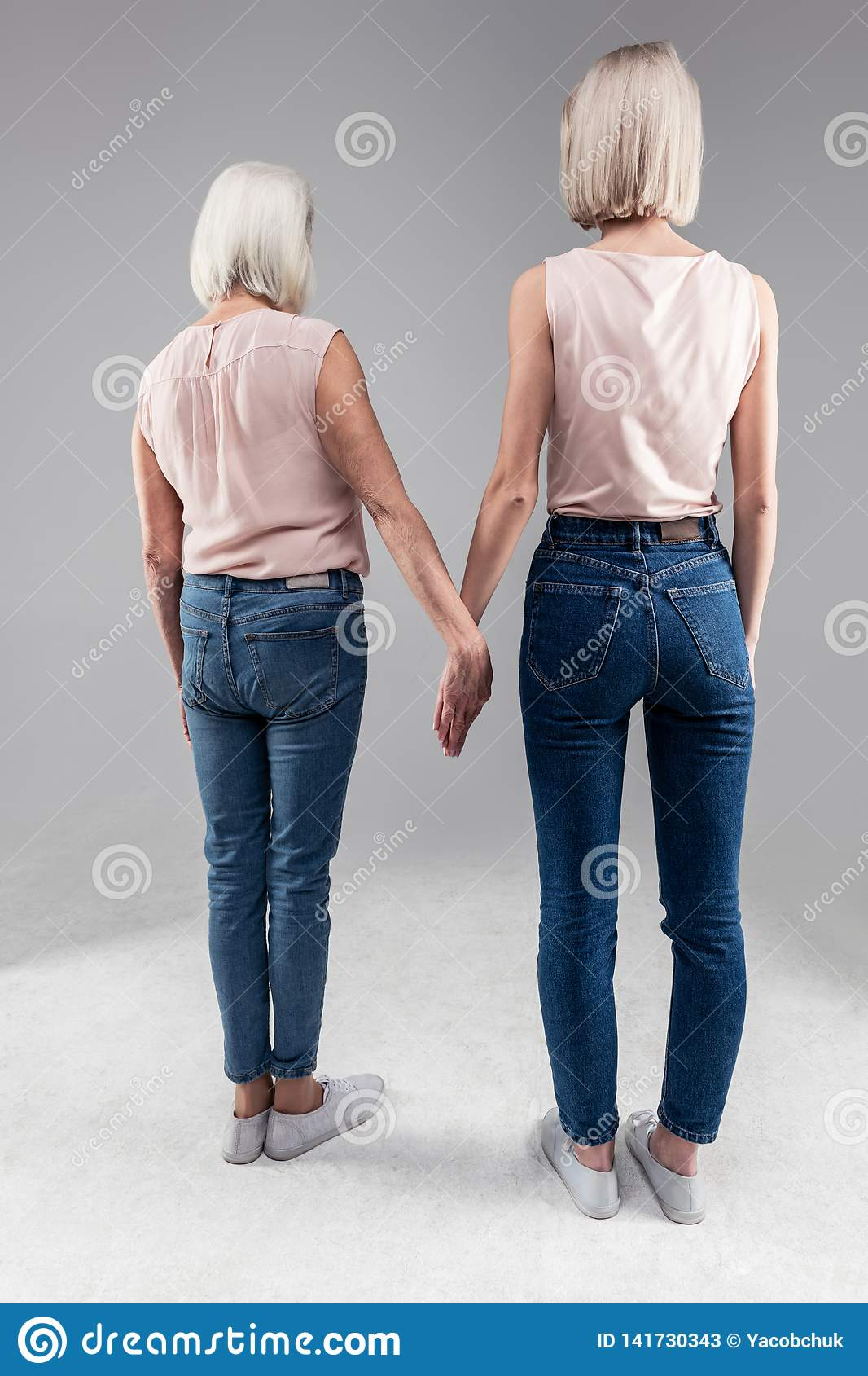 Blonde short-haired girls standing with her old mother and holding her hand