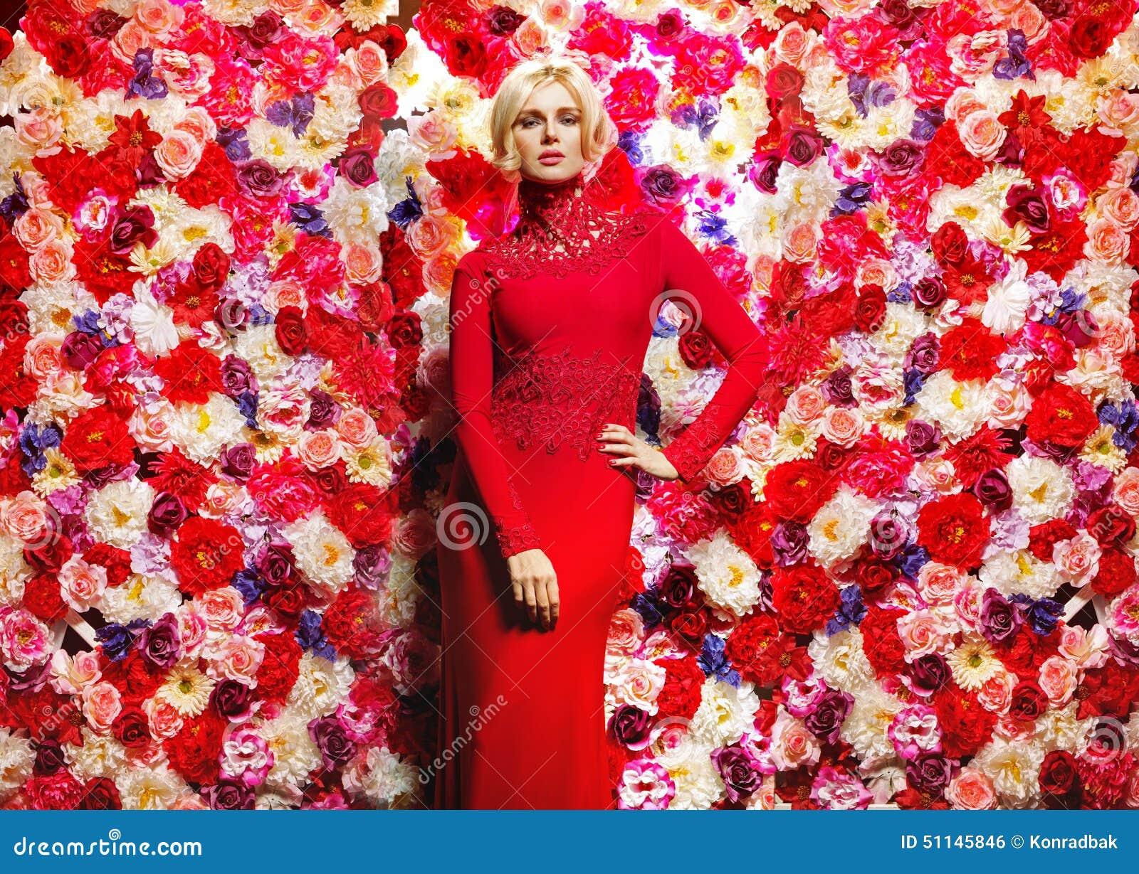 Blonde slanke vrouw over de bloemmuur