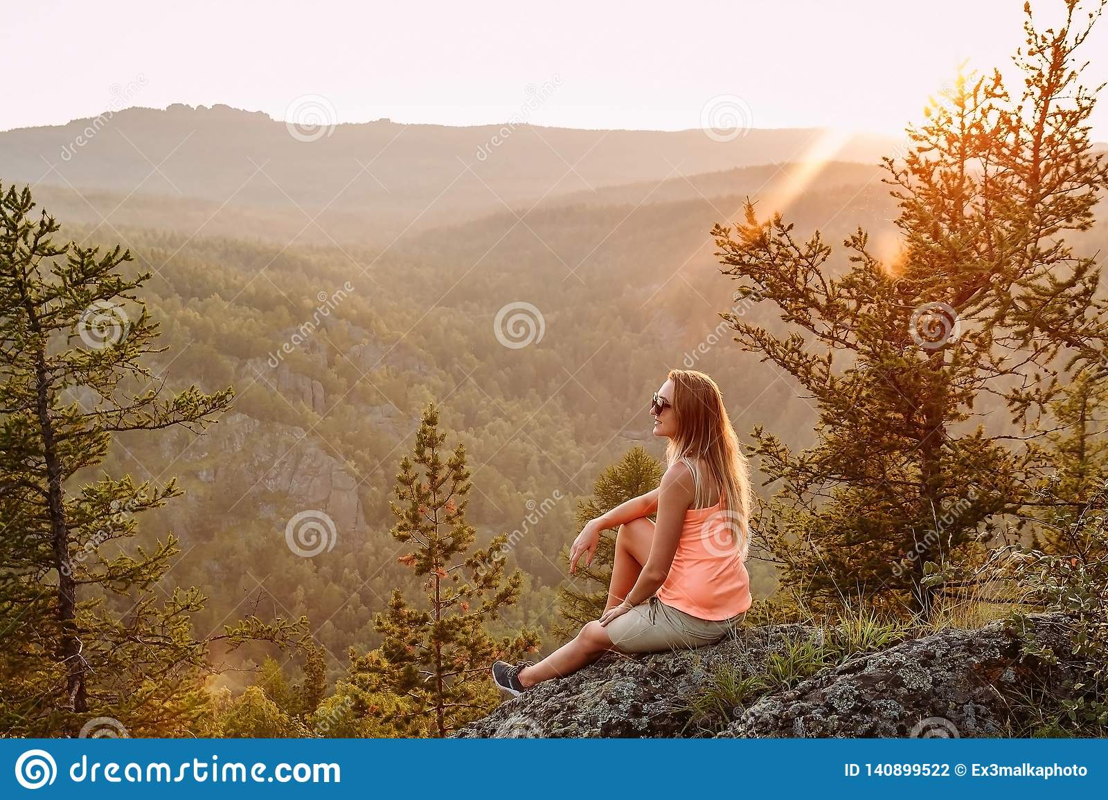 Blonde slender woman tourist in an orange t-shirt in the mountains in the summer at sunset. beautiful landscape of the Ural