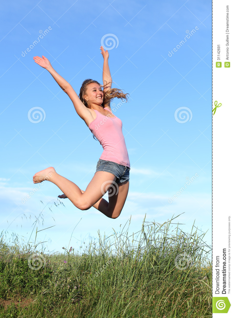 blonde teenager girl jumping happy in the mountain stock
