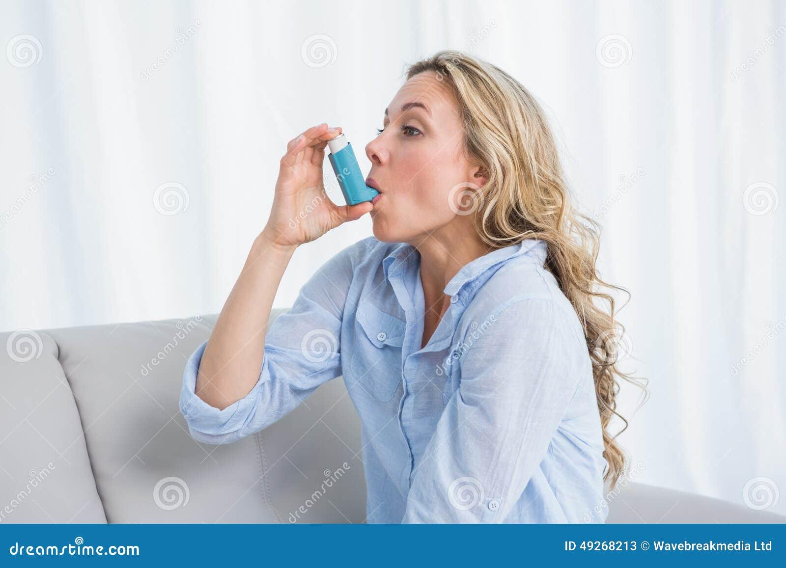 Blonde using her asthma inhaler on couch
