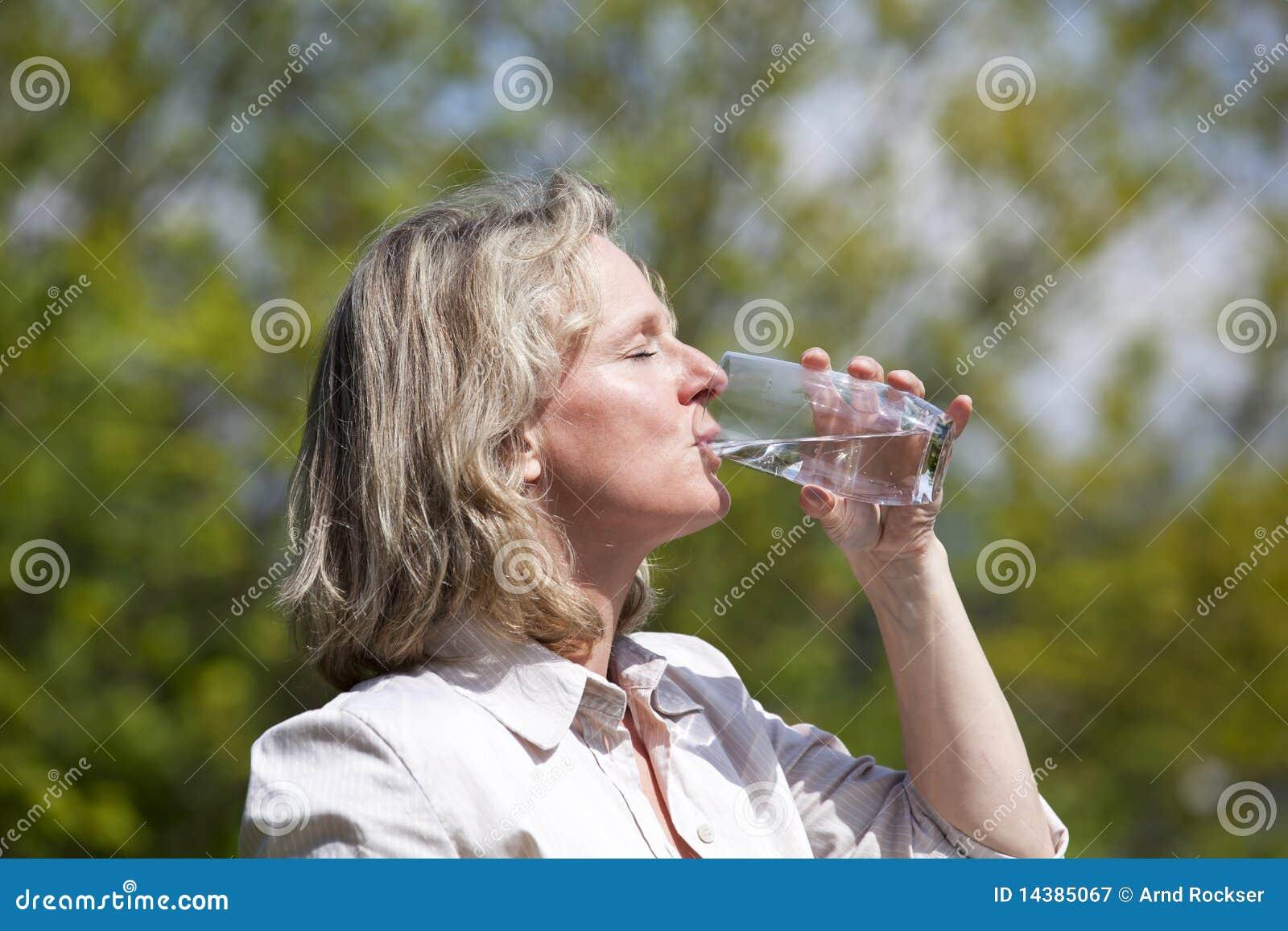 Blonde vrouw die een glas water drinkt