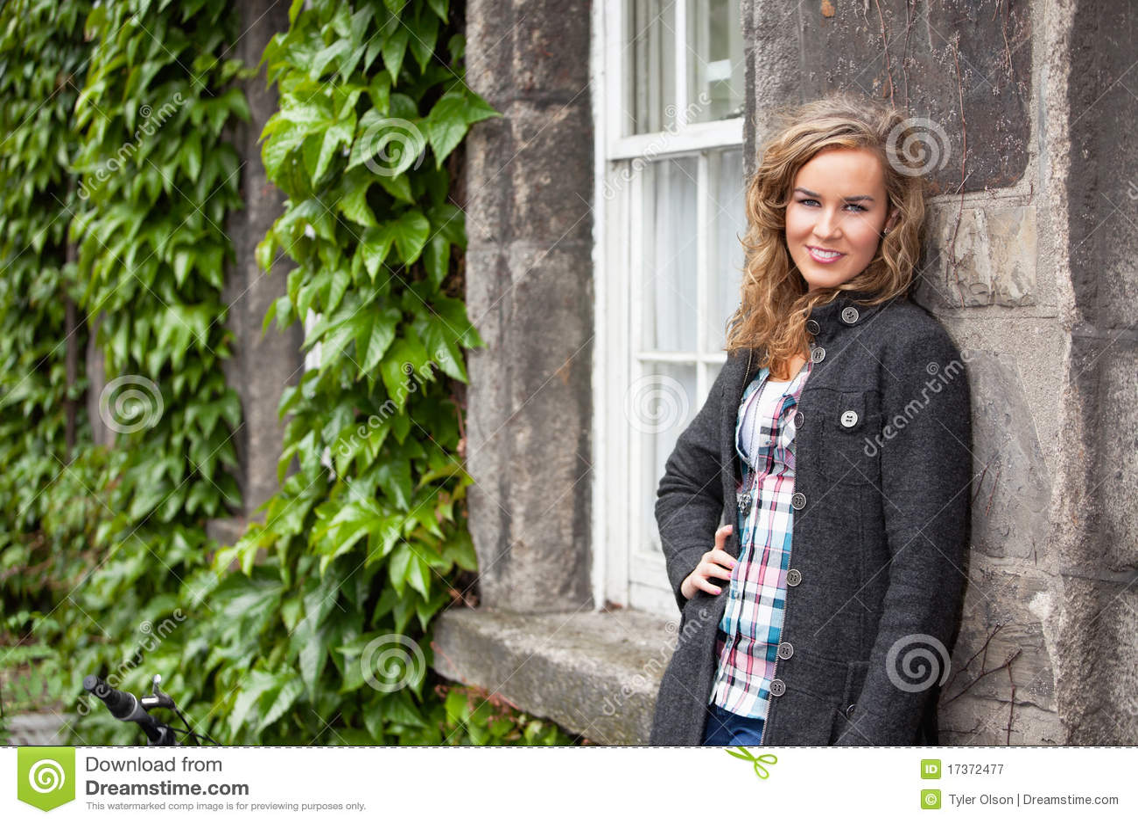 Blonde vrouw die tegen steenmuur leunt