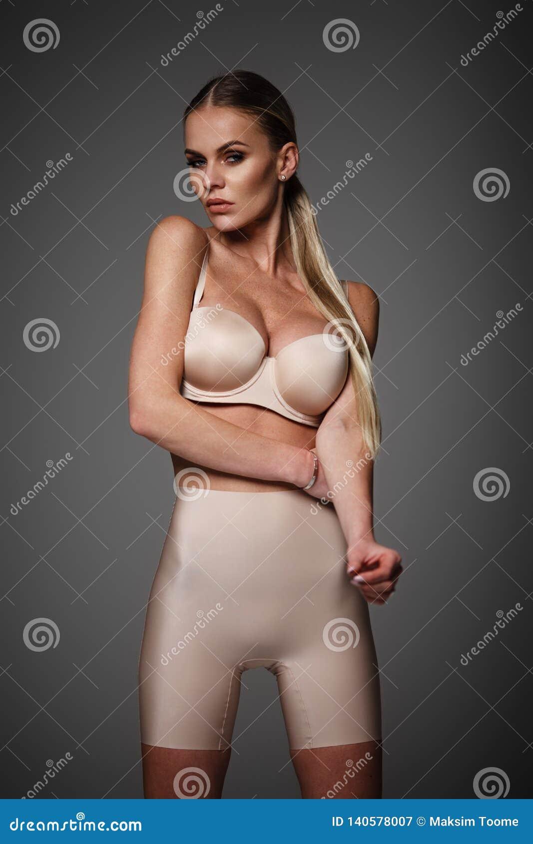 Blonde vrouw in lingerie en legging het stellen
