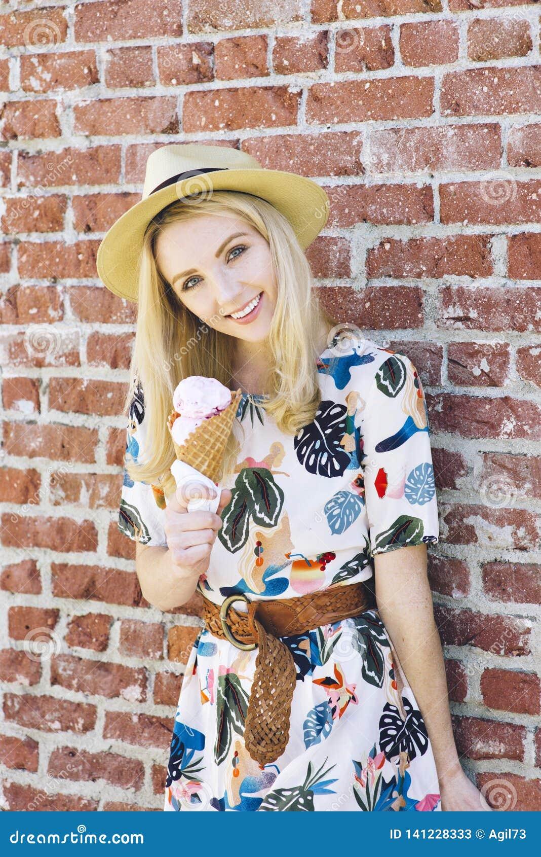 Blonde Vrouwentribunes tegen een Bakstenen muur met een Roomijskegel die Fedora Outdoors in de Zomer dragen
