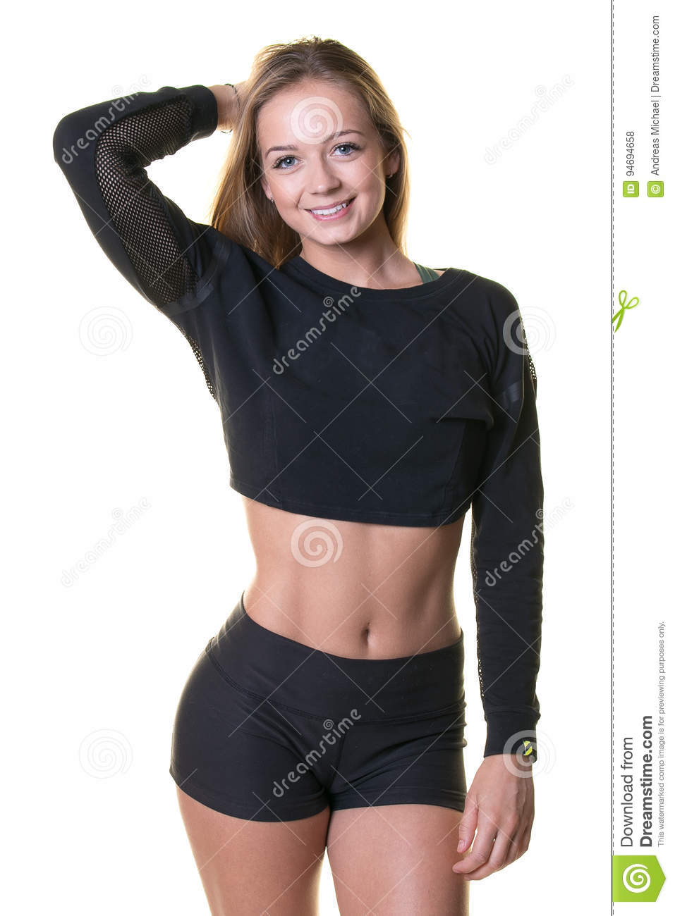 9a2538f703f17 A beautiful young blonde woman in a black crop top and black shorts isolated  on a white background.
