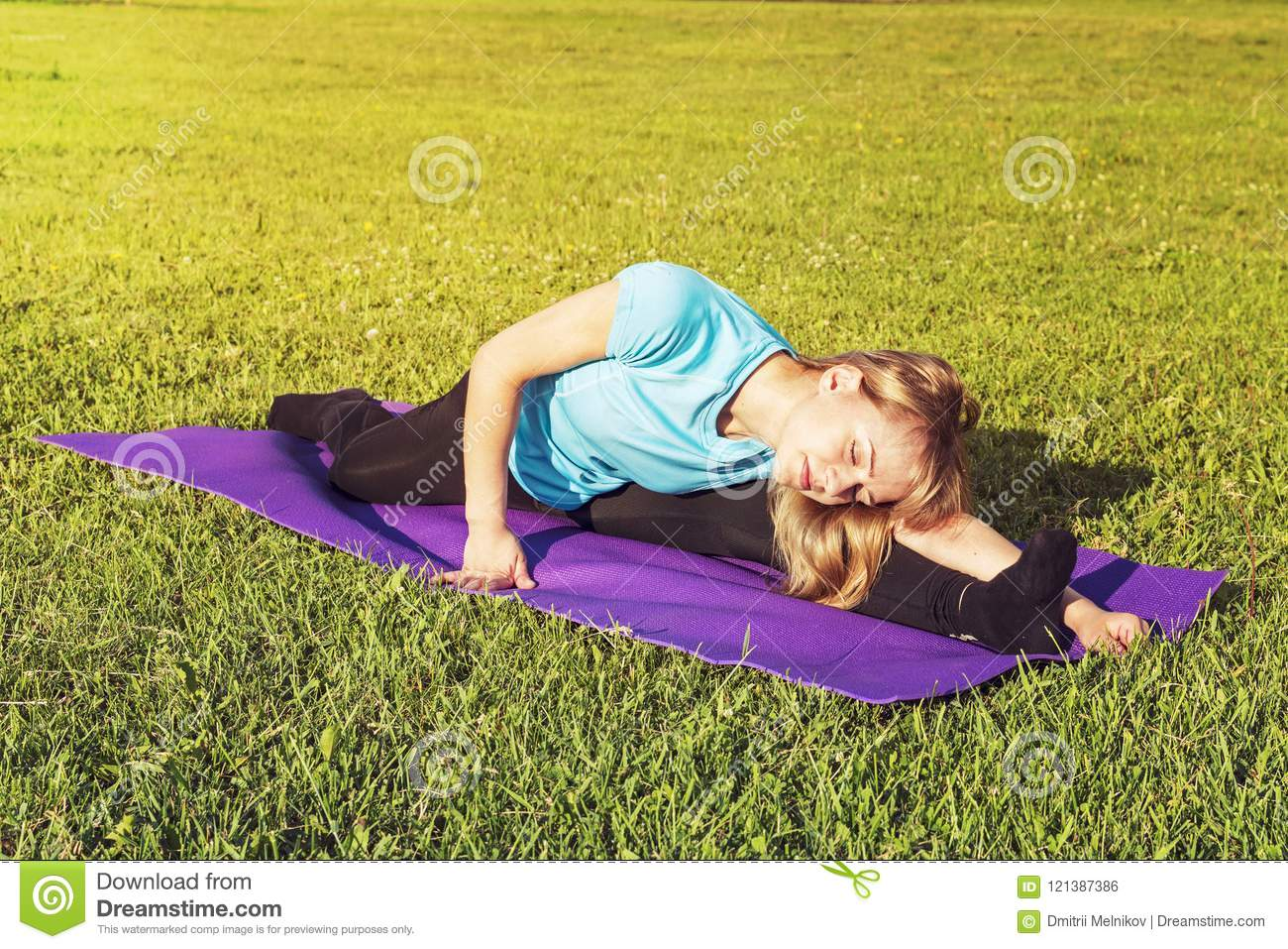 Blonde woman coach in a sporty short top and gym leggings makes a wide twine on the rug for yoga hands are raised