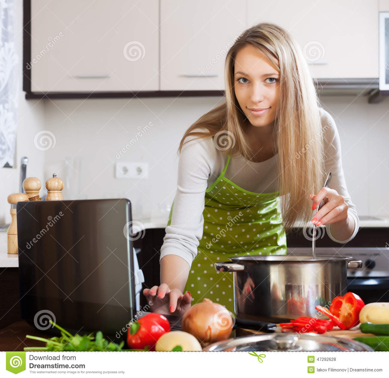 Women Kitchen: Blonde Woman Cooking Soup With Laptop Stock Photo