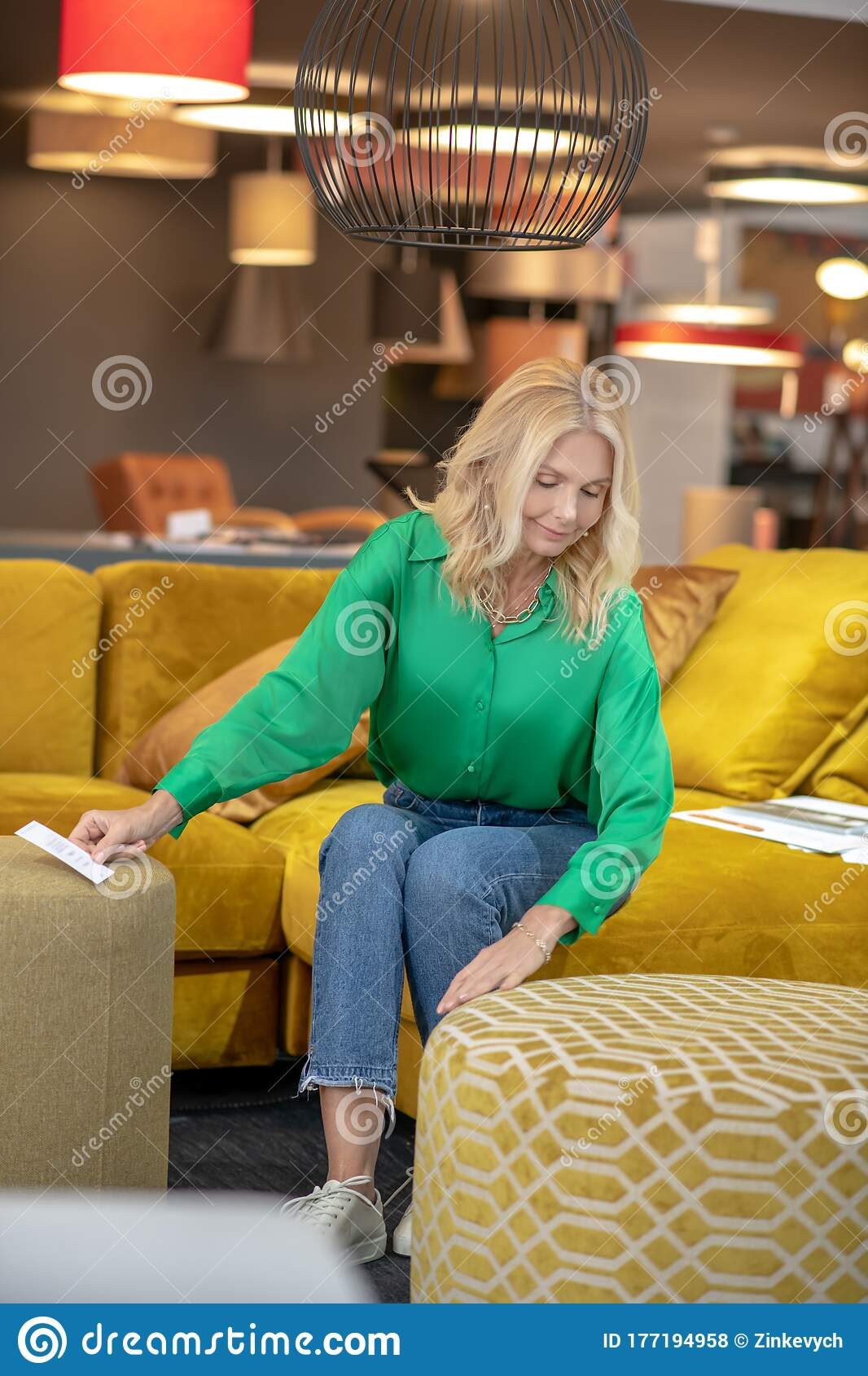 Picture of: Blonde Woman In A Green Blouse And Jeans Sitting On A Yellow Sofa Stock Photo Image Of Blonde Involved 177194958