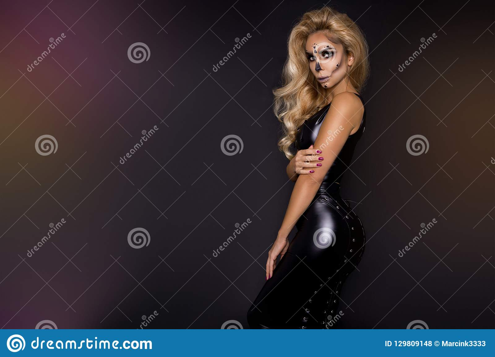 Blonde woman in Halloween makeup and leather outfit on a black background in the studio. Skeleton, monster and witch.