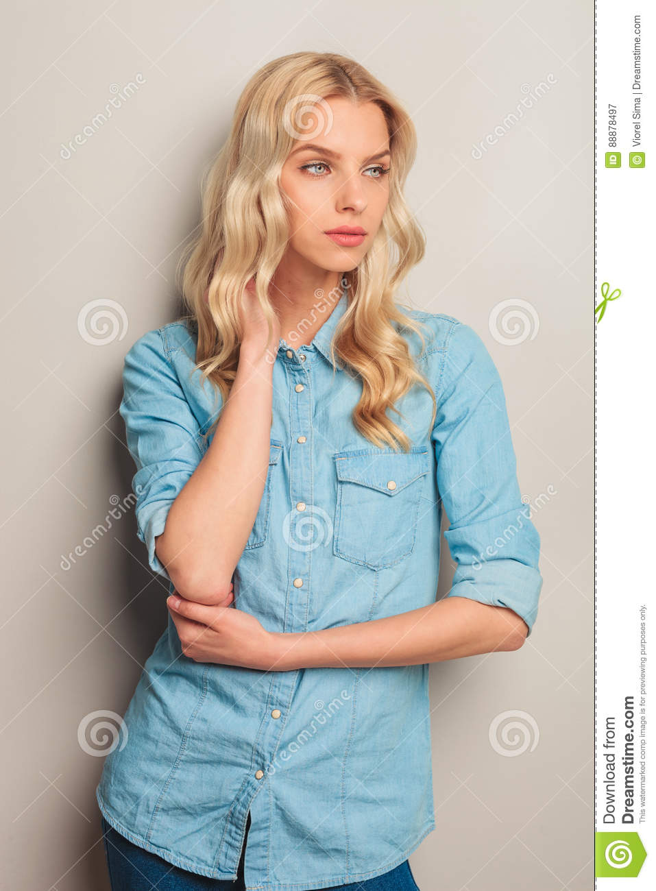 Blonde Woman Holding Hand On Neck And Looks To Side Stock