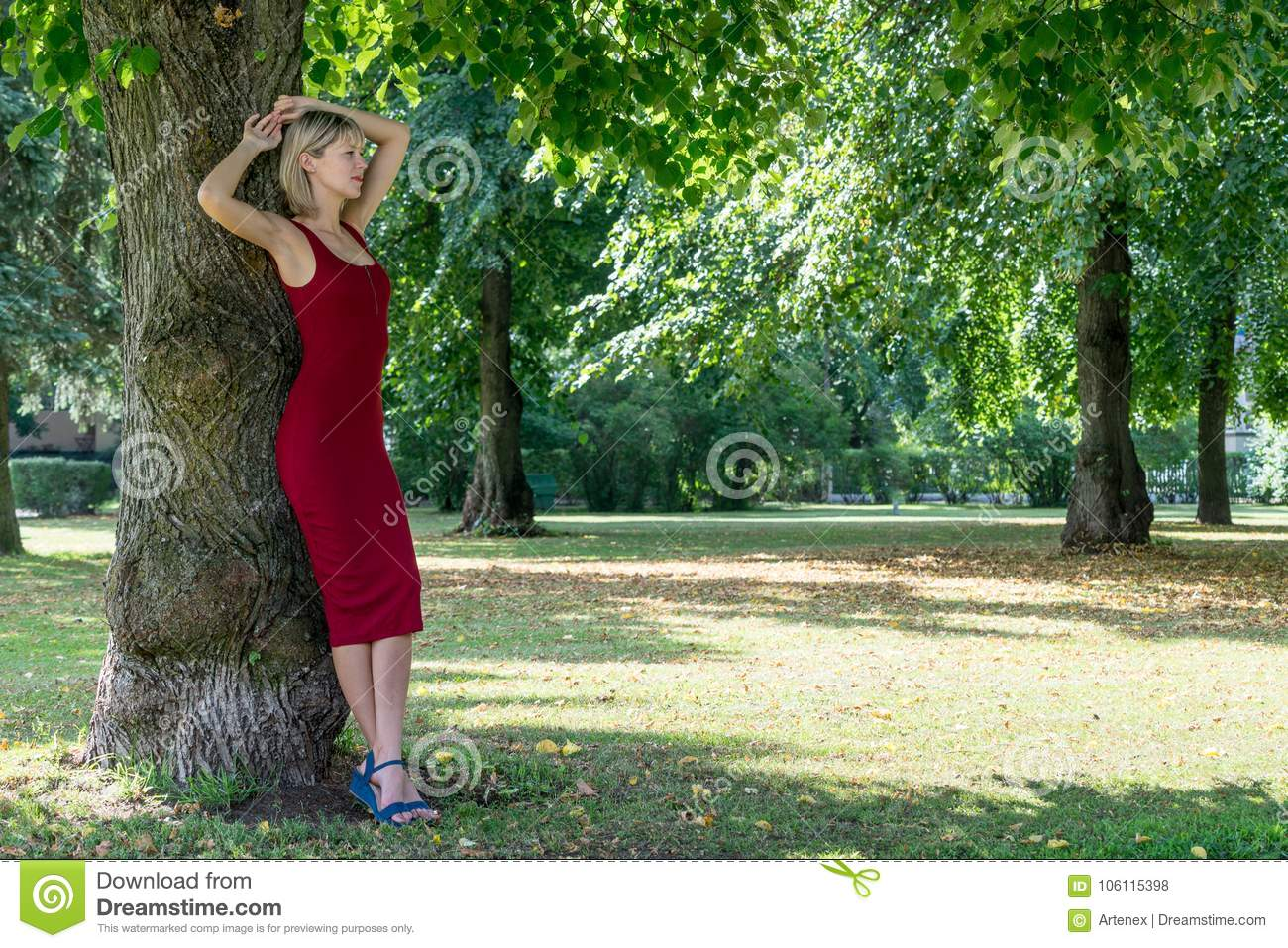 Blonde woman hugging a tree in park. Young girl in a red dress resting in nature, leaned against a tree.