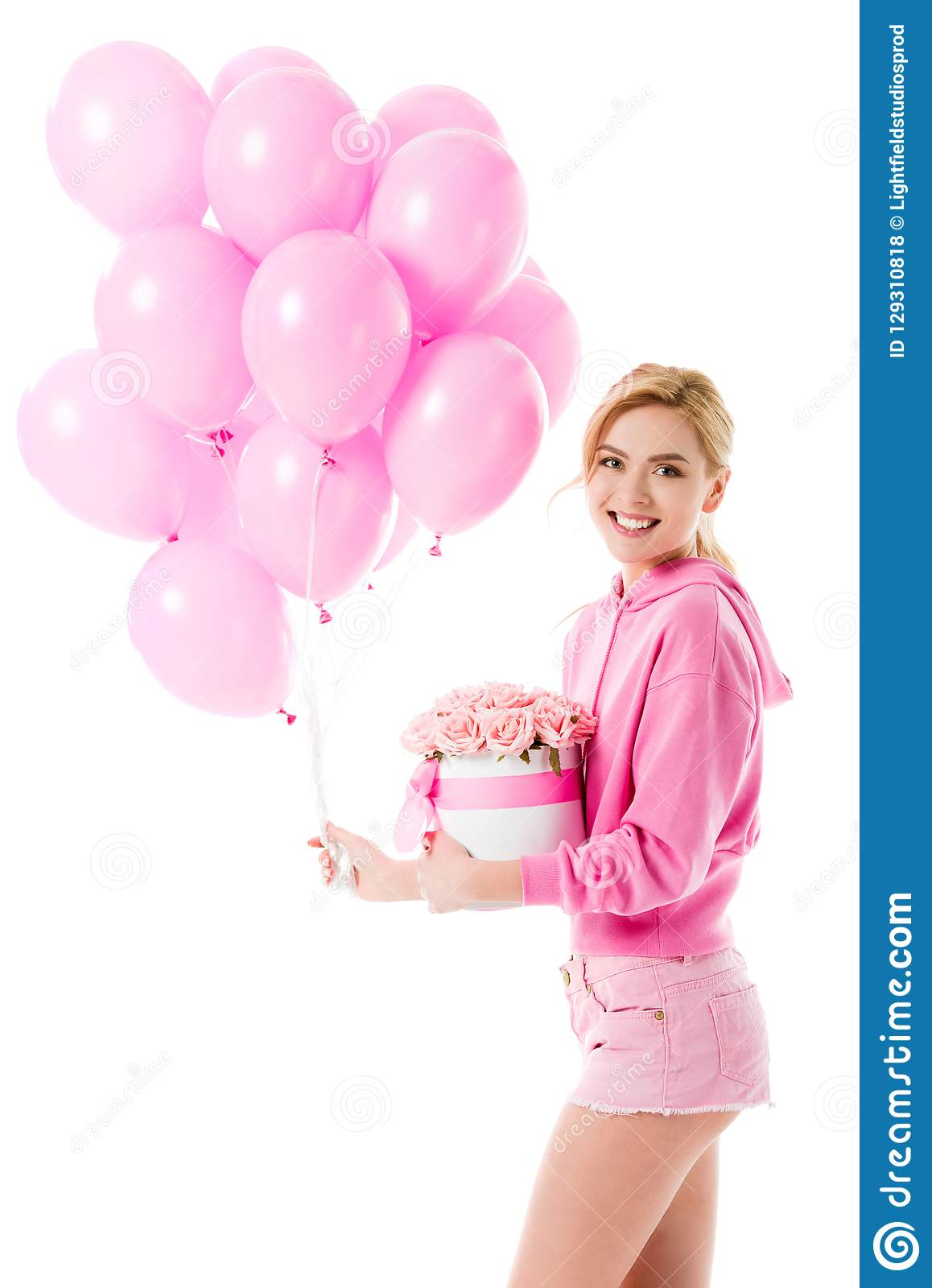 Blonde woman in pink clothes holding balloons with flowers